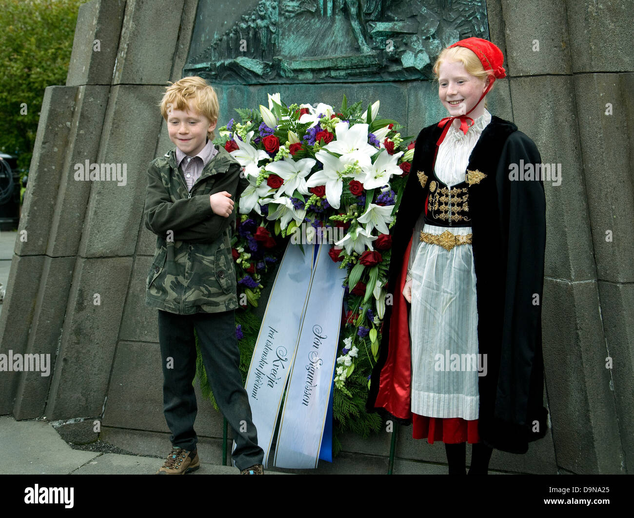 In Reykjavik, on Iceland's independence anniversary, two youngsters pose at a memorial--the girl in national - Stock Image