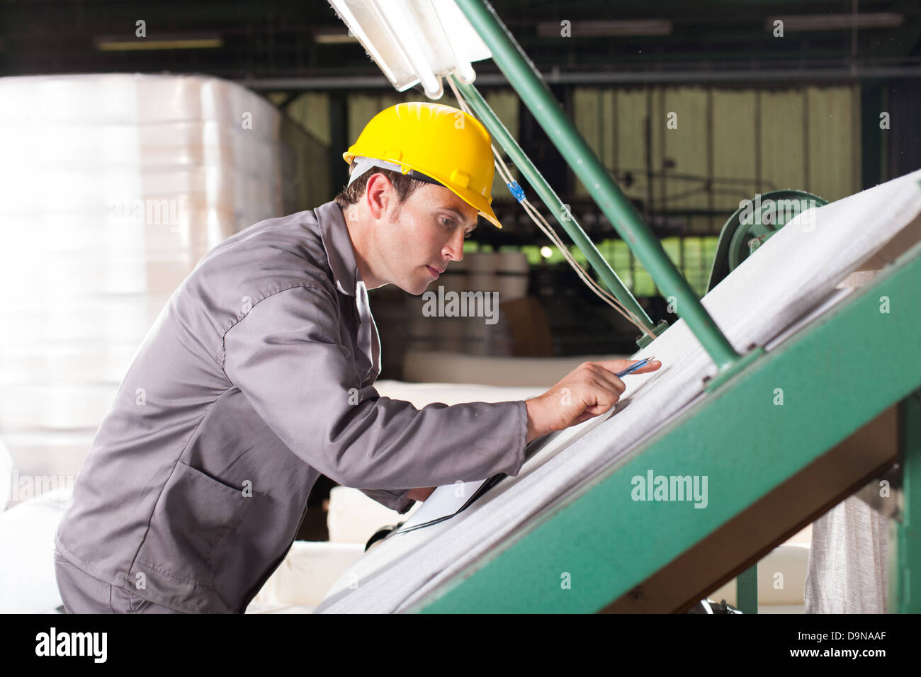 textile quality controller checking fabrics on QC table - Stock Image