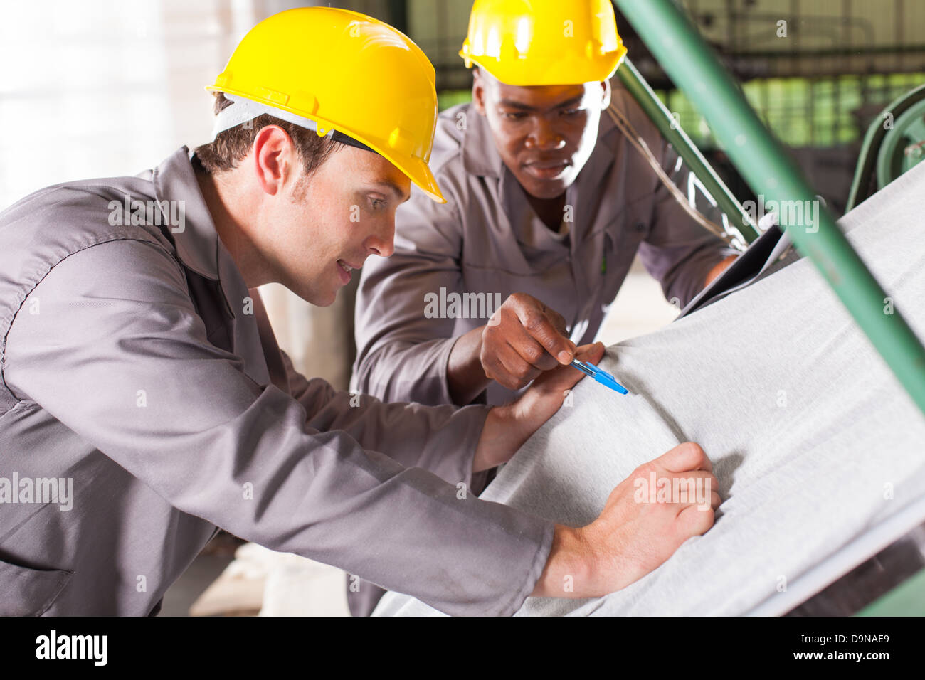 two textile workers checking fabrics quality on QC table - Stock Image