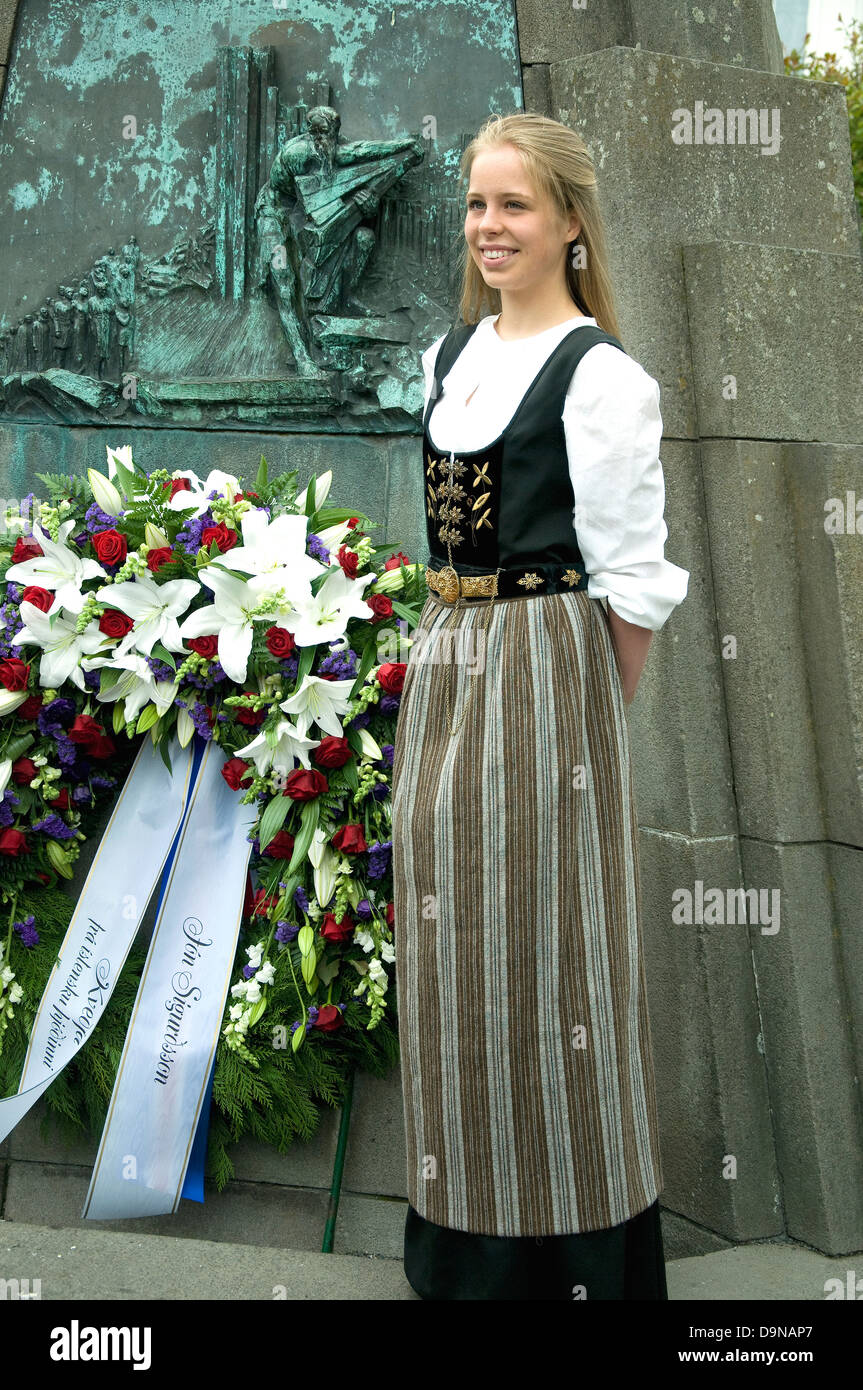 In Iceland's National Day a young woman wearing national dress poses beside a memorial in Reykjavik Stock Photo