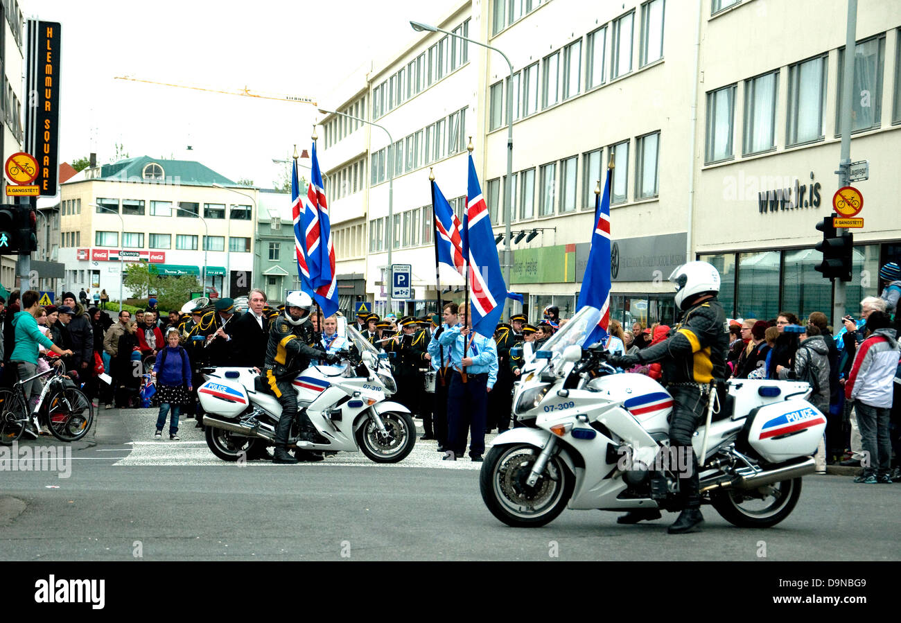 On Iceland's National Day police motorcyclists control traffic to allow a Scout parade to march in Reykjavik's - Stock Image