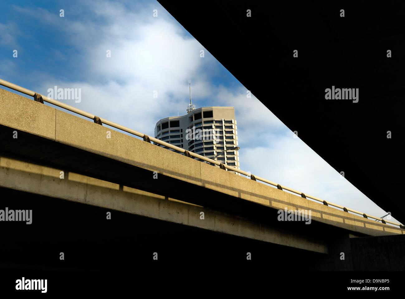 Building visible between freeway flyovers. Perth, Western Australia, Australia - Stock Image