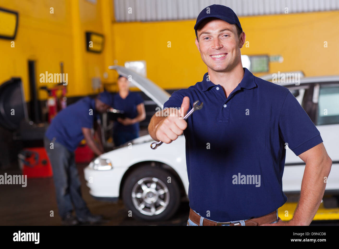 happy male auto mechanic giving thumb up holding wrench - Stock Image