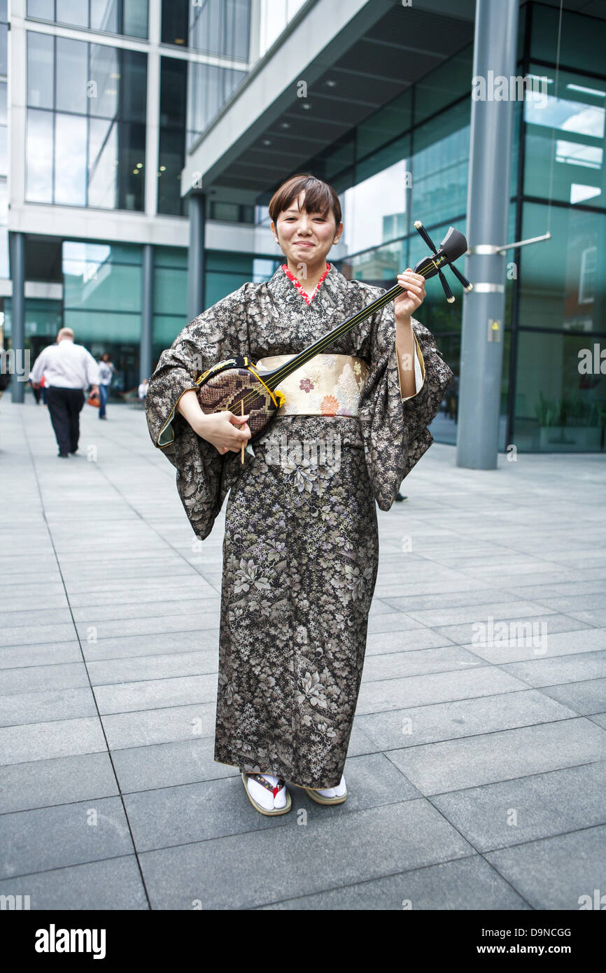 Sanshin - three stringed traditional musical instrument from Okinawa being shown by a Japanese female wearing a - Stock Image