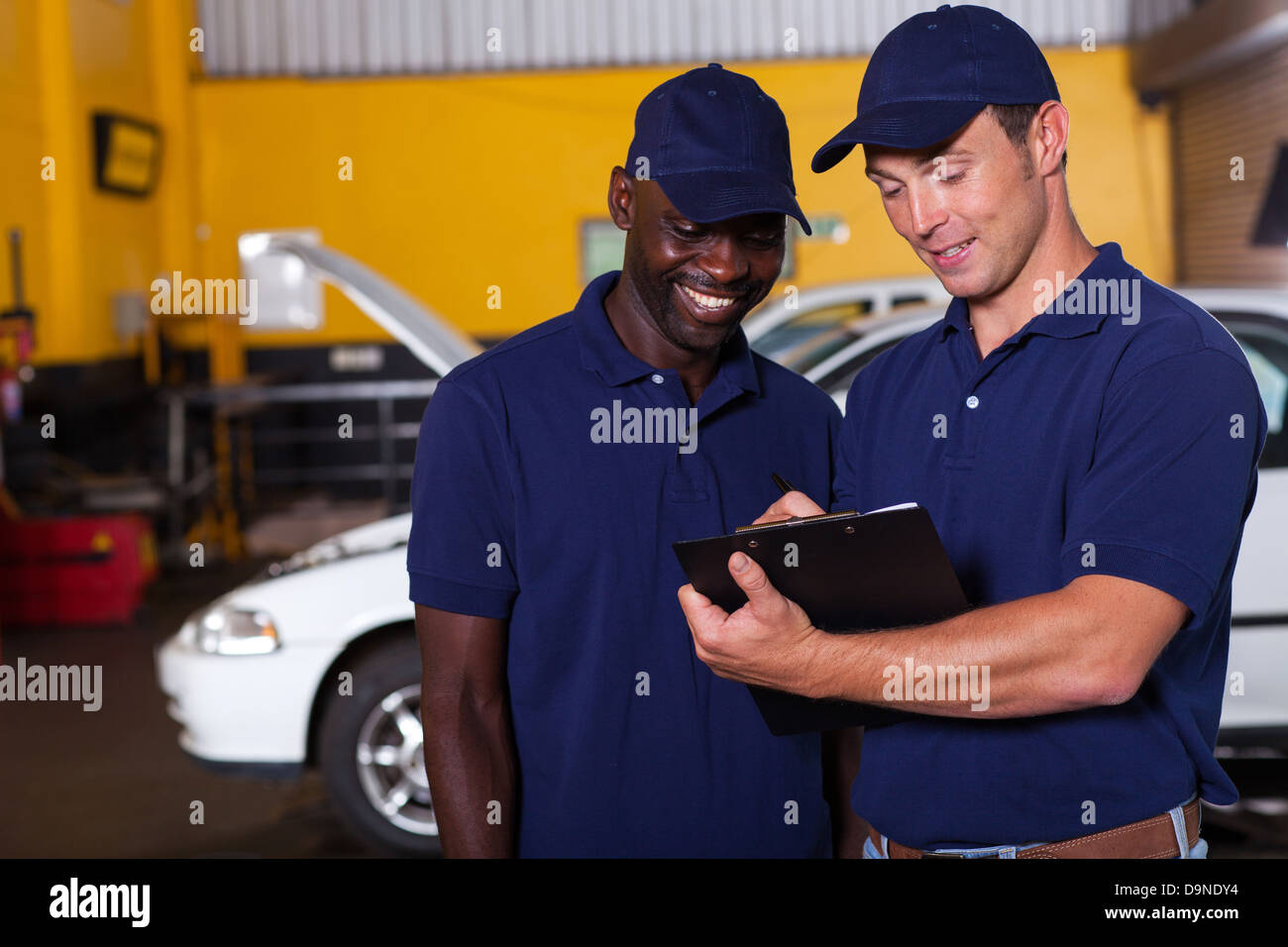 two happy auto mechanics going through checklist inside workshop - Stock Image
