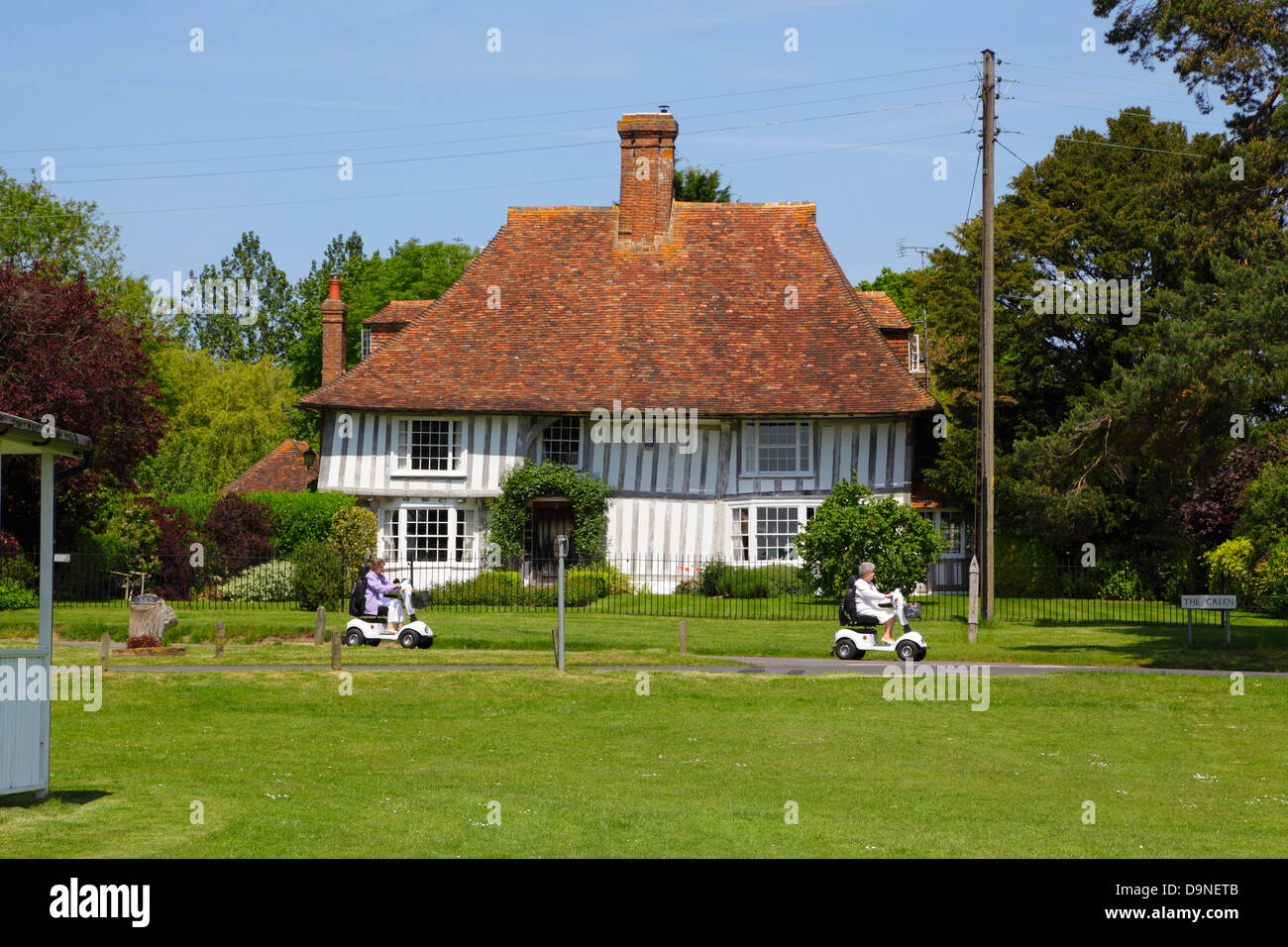 Two ladies on mobility scooters riding along The Green, Woodchurch Kent England UK GB - Stock Image