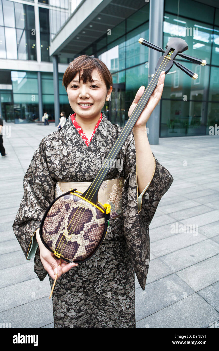 Sanshin a three stringed traditional musical instrument from Okinawa being shown by a Japanese female wearing a - Stock Image