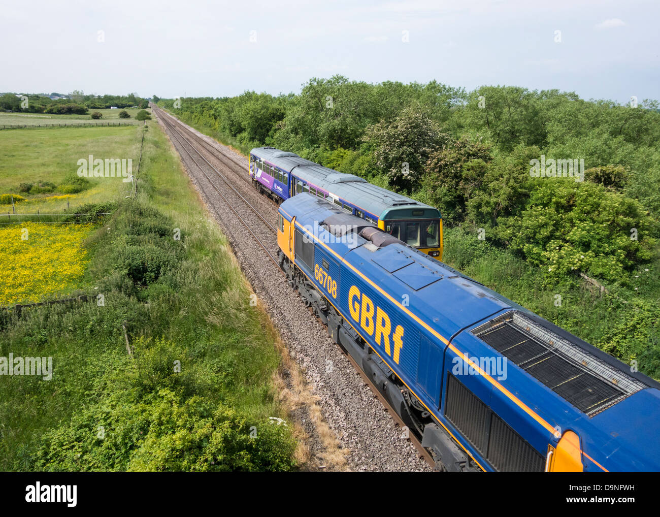 GBR Freight train and Northern Rail passenger train on Northern Rail line near Billingham, north east England, UK - Stock Image