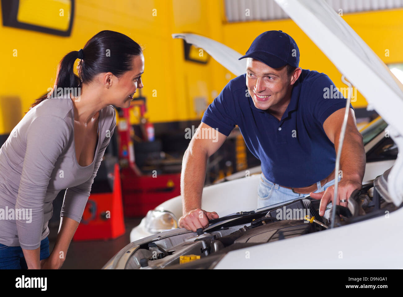 trustworthy auto technician talking to female customer in garage - Stock Image
