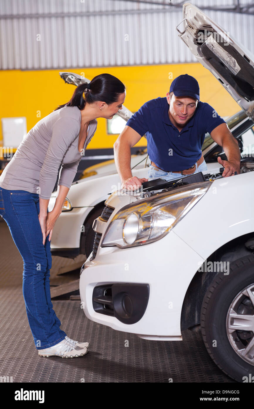 auto mechanic talking to female customer in front of her car with bonnet open Stock Photo