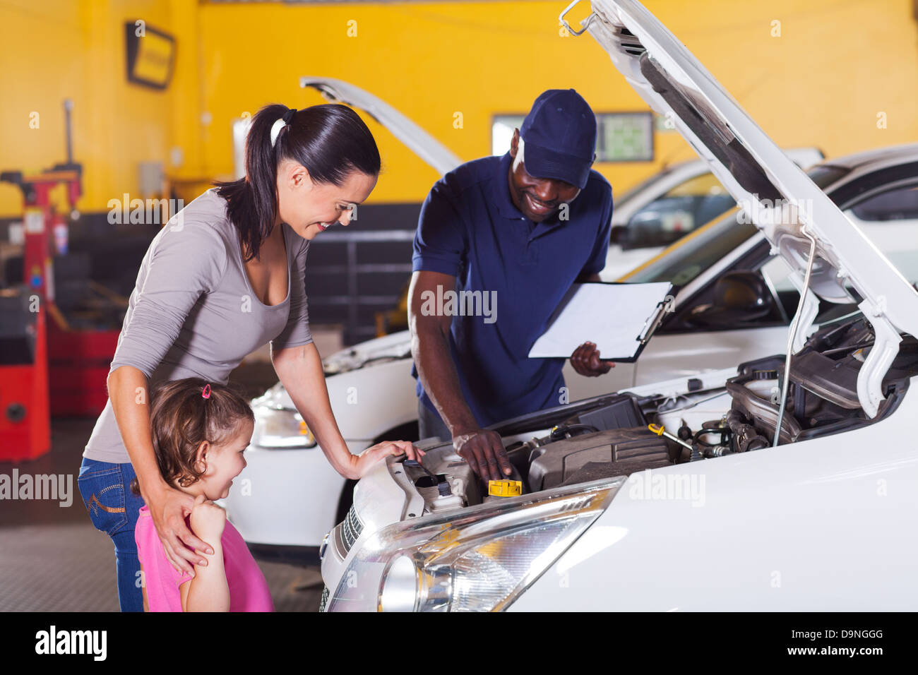 happy mother and little girl in car service center with auto technician Stock Photo