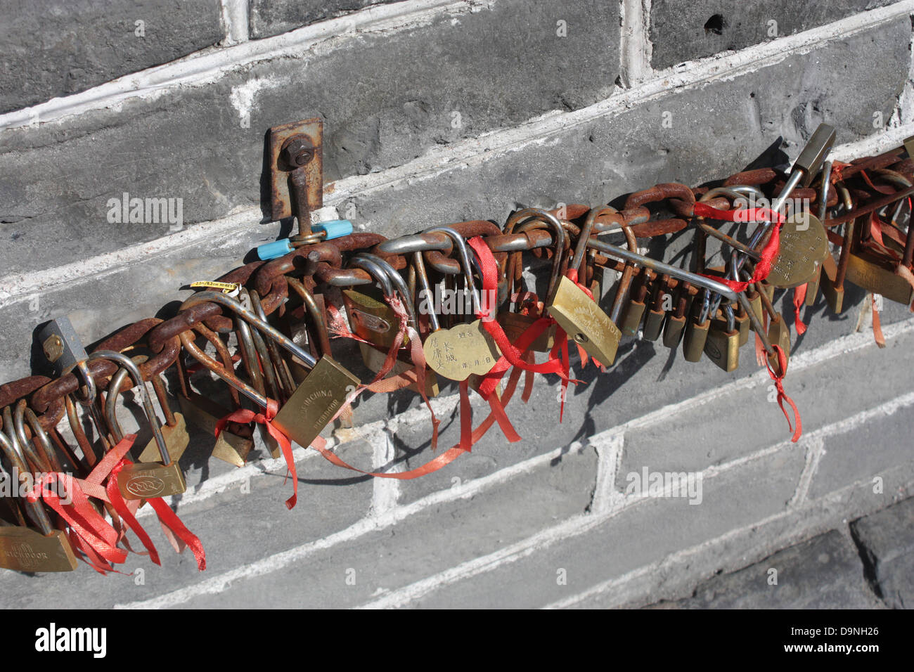 Keys and padlocks chained to the Great Wall of China along with red ribbons represent good luck charms and key symbolism. - Stock Image