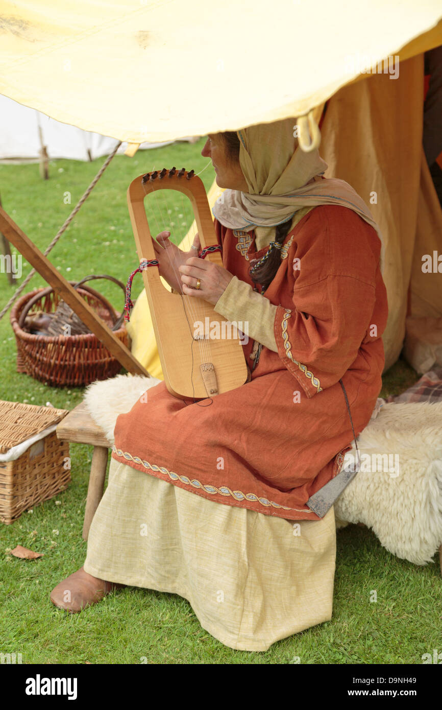 Reenactment of life in a Viking village, woman playing musical instrument, Peterborough Heritage Festival 22 June - Stock Image