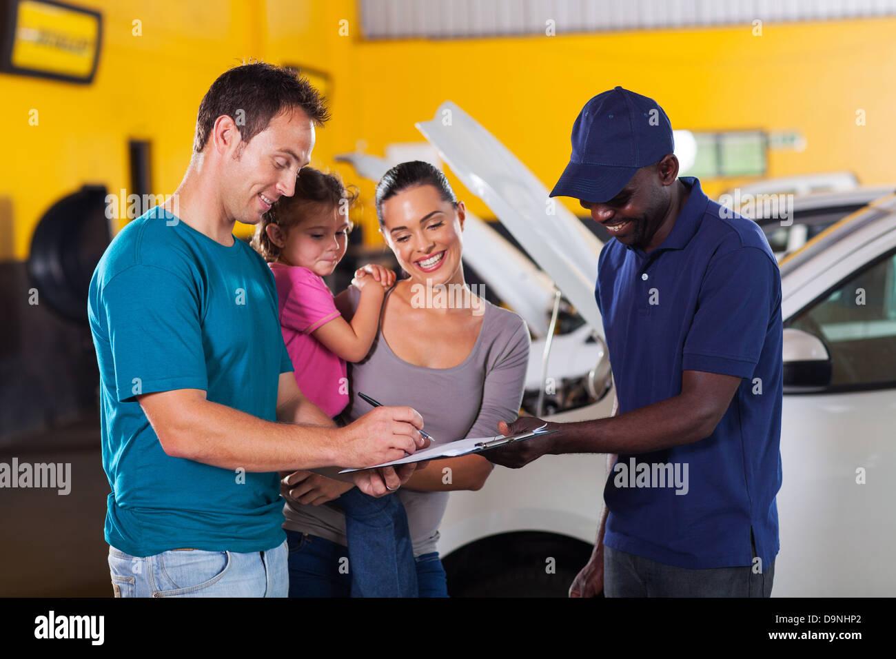happy family man signing invoice in car repair shop - Stock Image