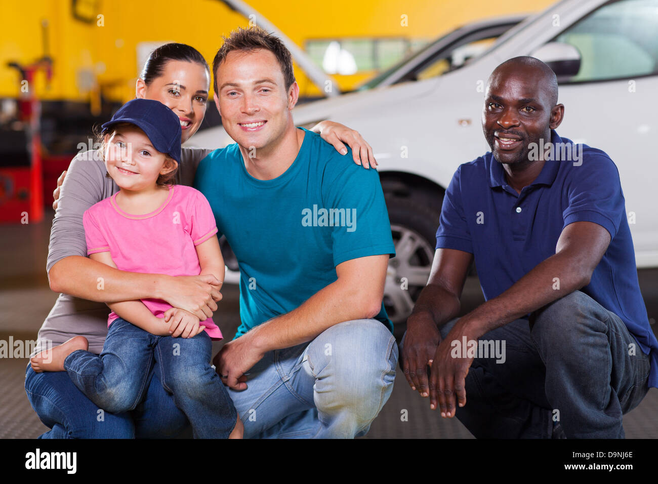 fun little girl wearing mechanic's cap in vehicle repair shop - Stock Image