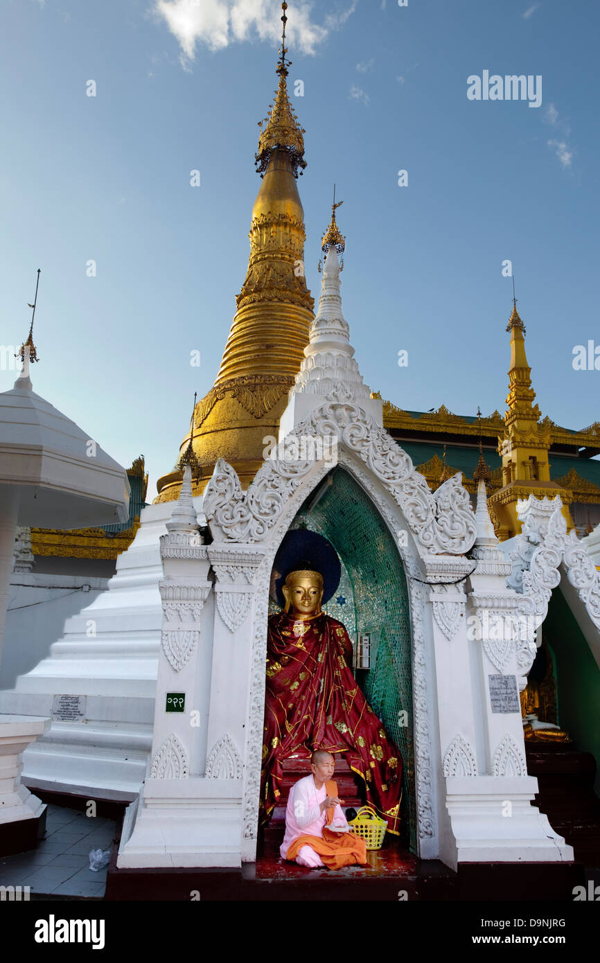 The Schwedagon, Burma's sacred temple in the heart of Rangoon. A nun in her pink robe eats before a Buddha in - Stock Image