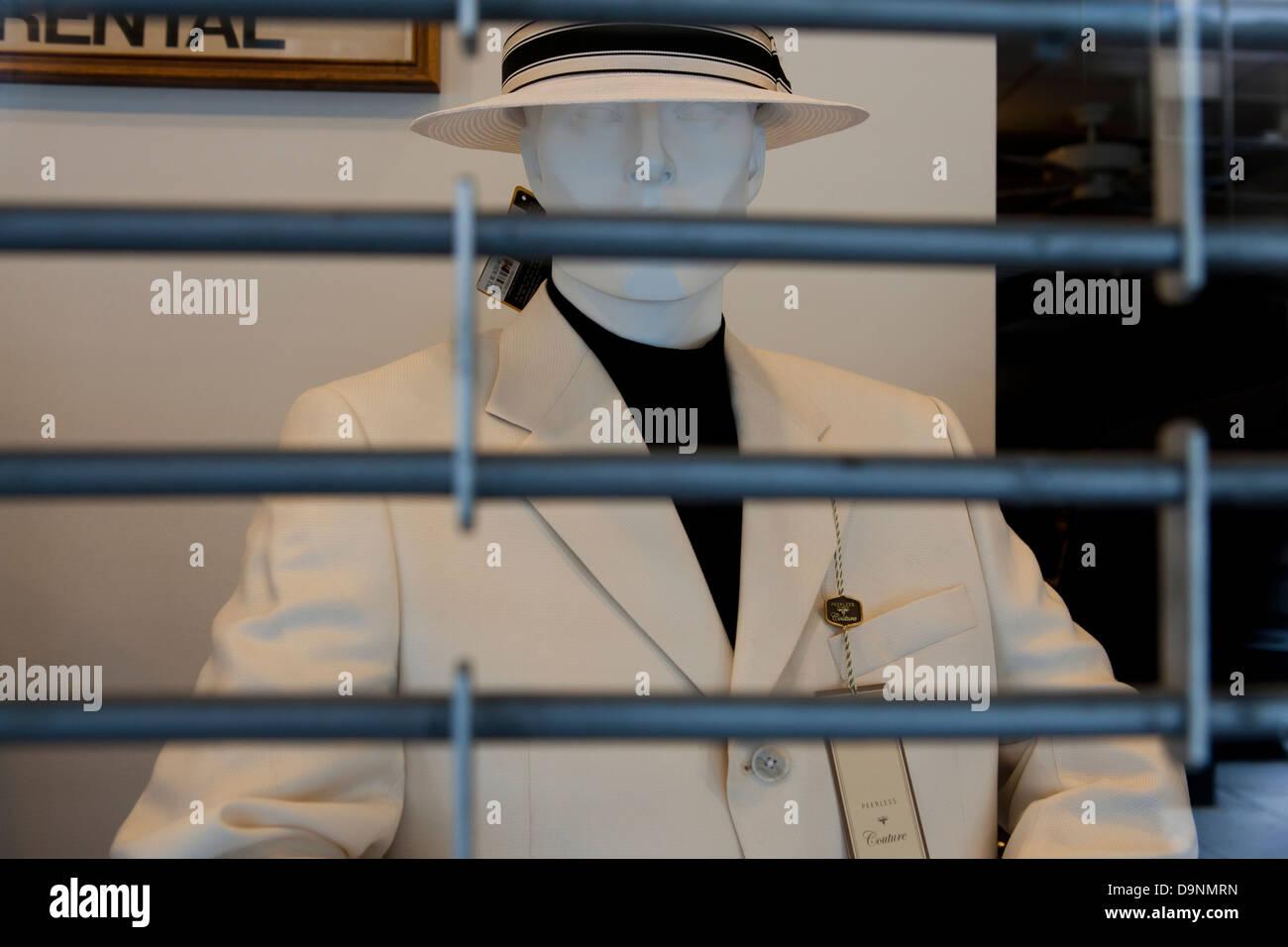 Men's business attire on mannequin behind barred shutter - Stock Image
