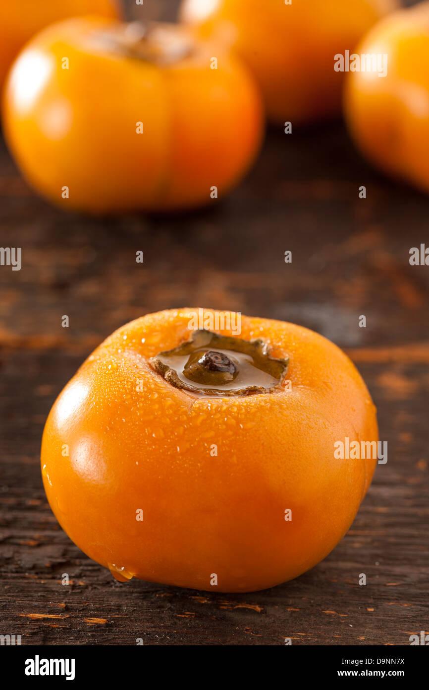 Organic Orange Persimmon Fruit against a background - Stock Image
