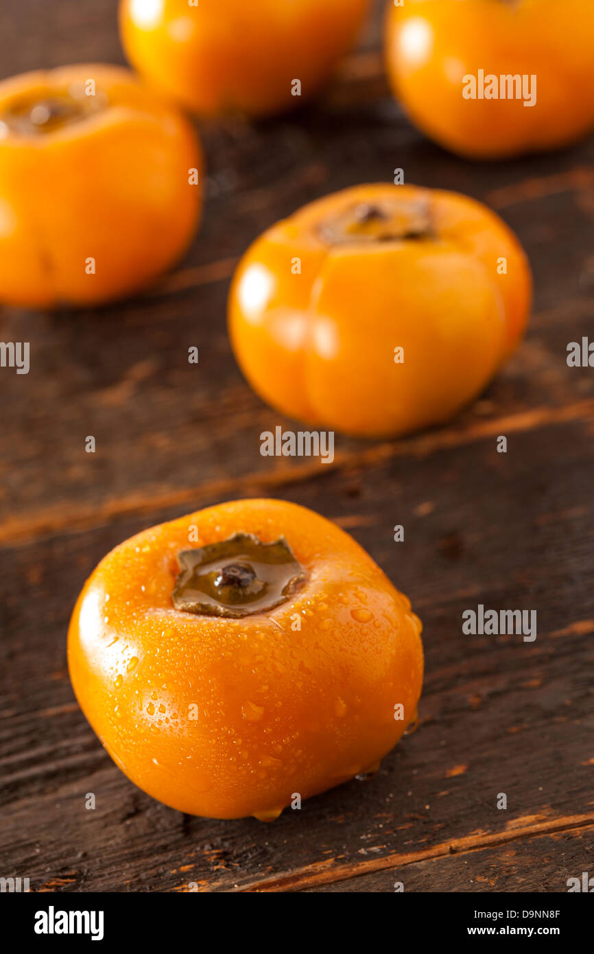 Organic Orange Persimmon Fruit against a background - Stock Image