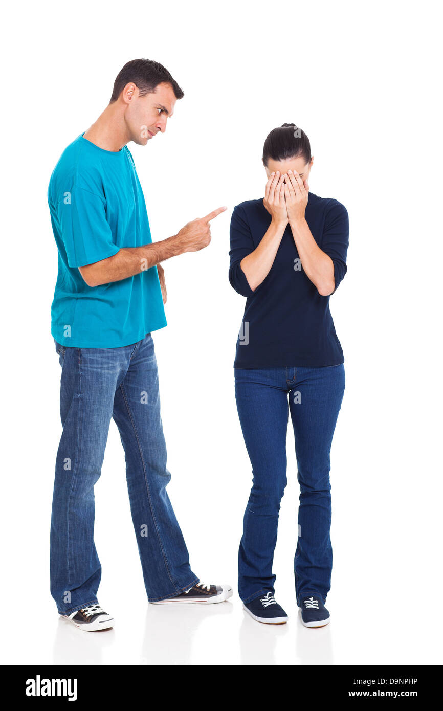 angry boyfriend pointing his crying girlfriend over white background - Stock Image