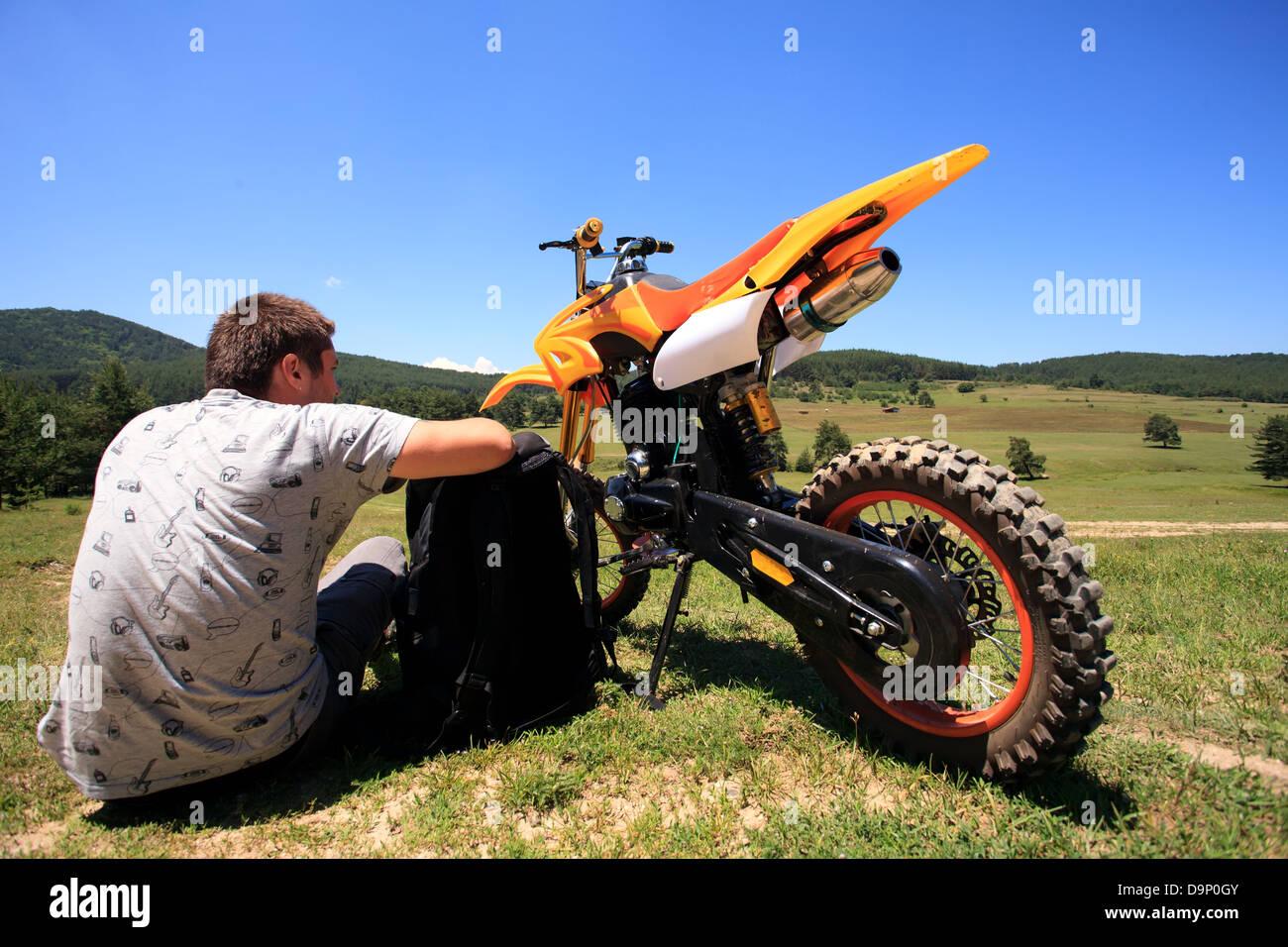 man siting near dirt bike in summer field - Stock Image
