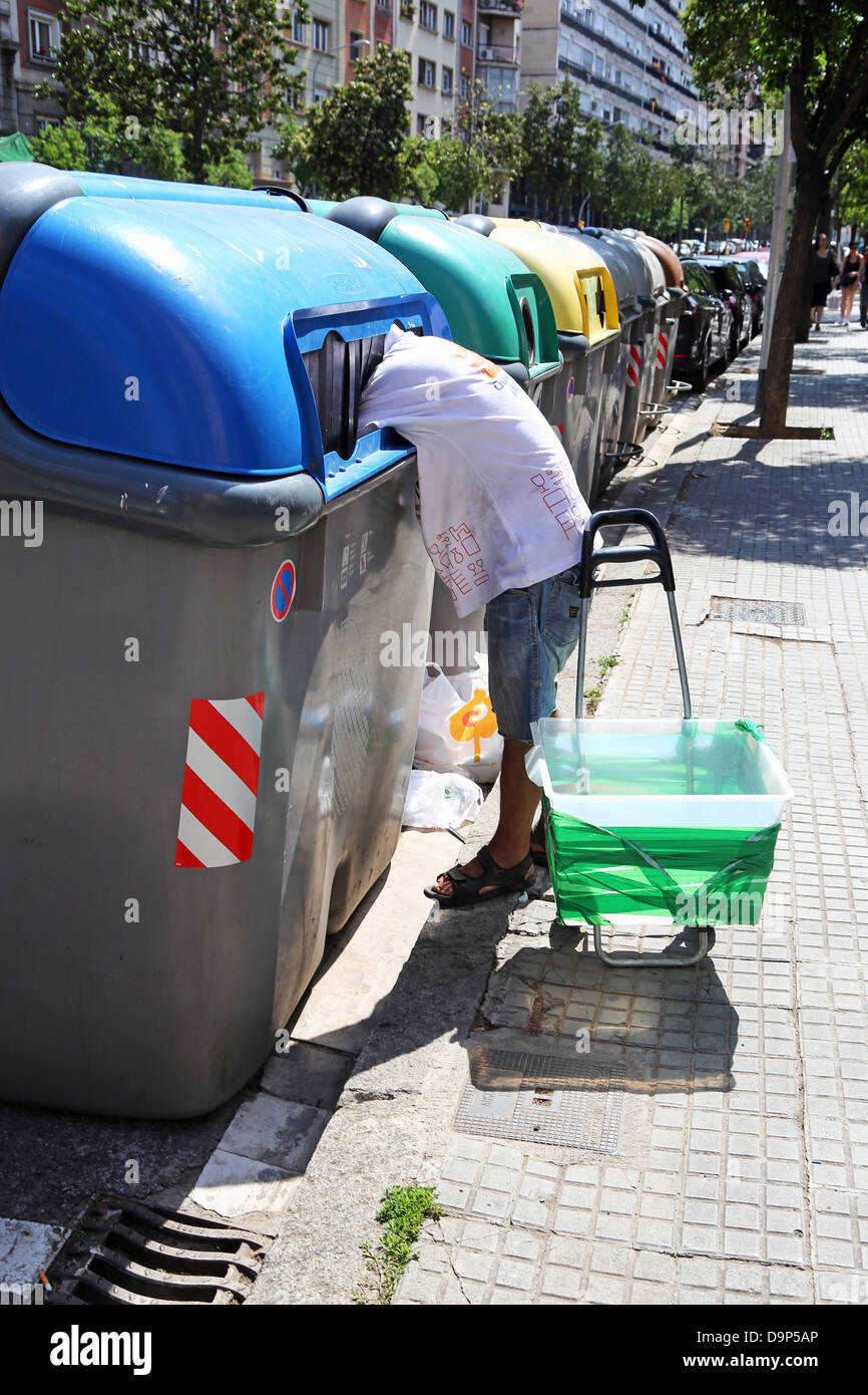 Man scavenging in recyling bins in Barcelona, Spain - Stock Image
