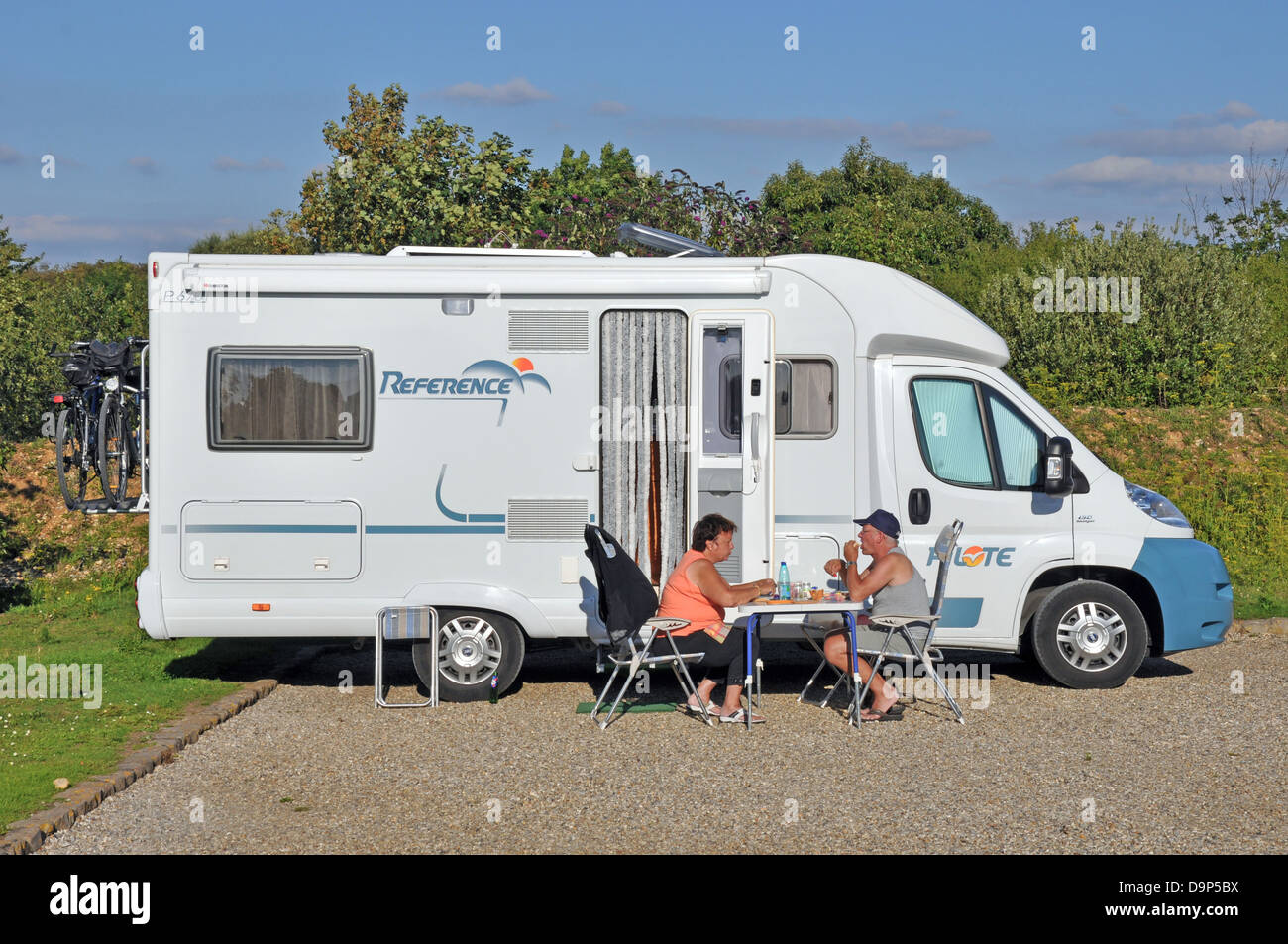 A couple eating in the sun outside their motorhome at the aire (stopping place) in Saint-Valery-sur-Somme, on the - Stock Image