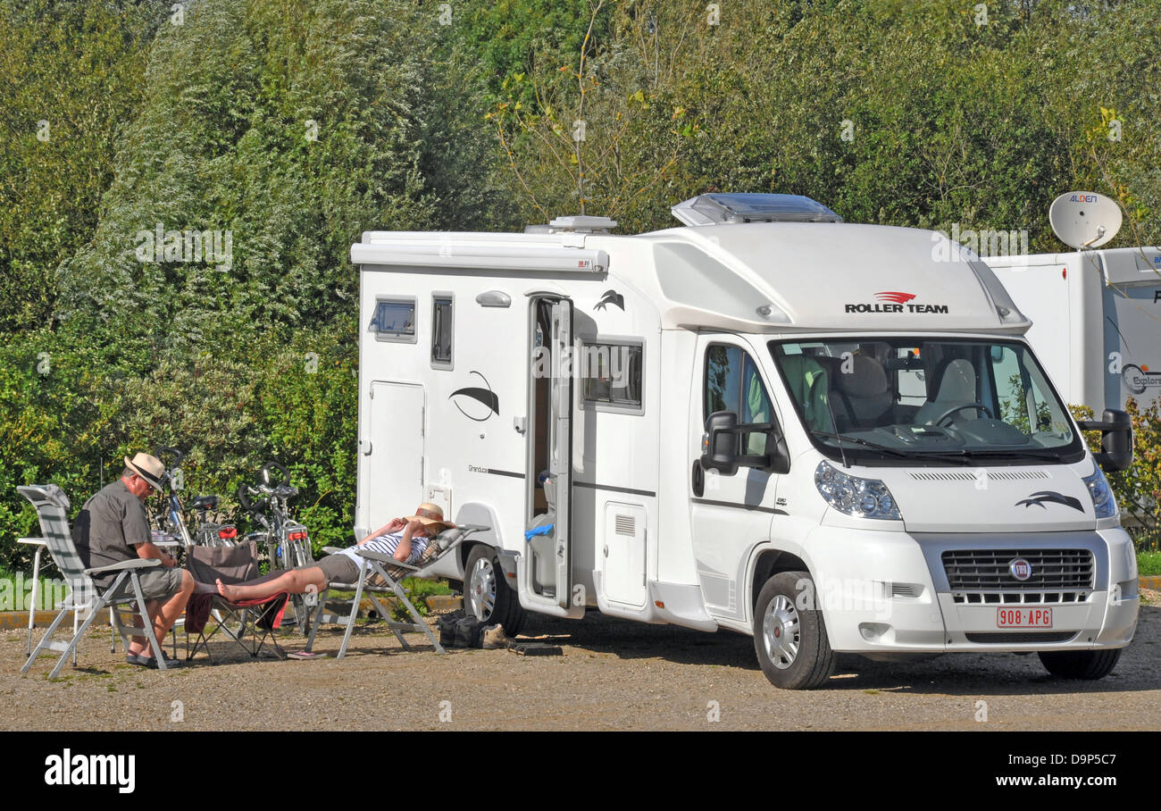 A couple relaxing in the sun outside their motorhome at the aire (stopping place) in Saint-Valery-sur-Somme, on - Stock Image