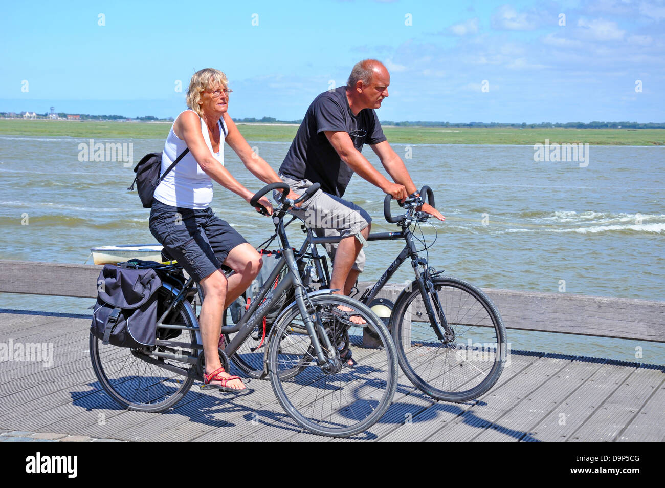 A middle aged couple cycling alongside the bay area of Saint-Valery-sur-Somme, on the northern coast of France, - Stock Image