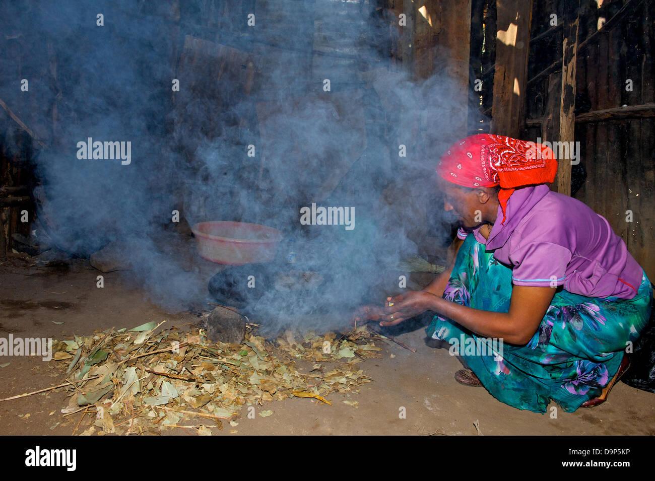 Die ehemalige arbeitslose Mimi Reta zündet ein Feuer in ihrer Hütte, um das traditionelle Fladenbrot (Njeera) - Stock Image