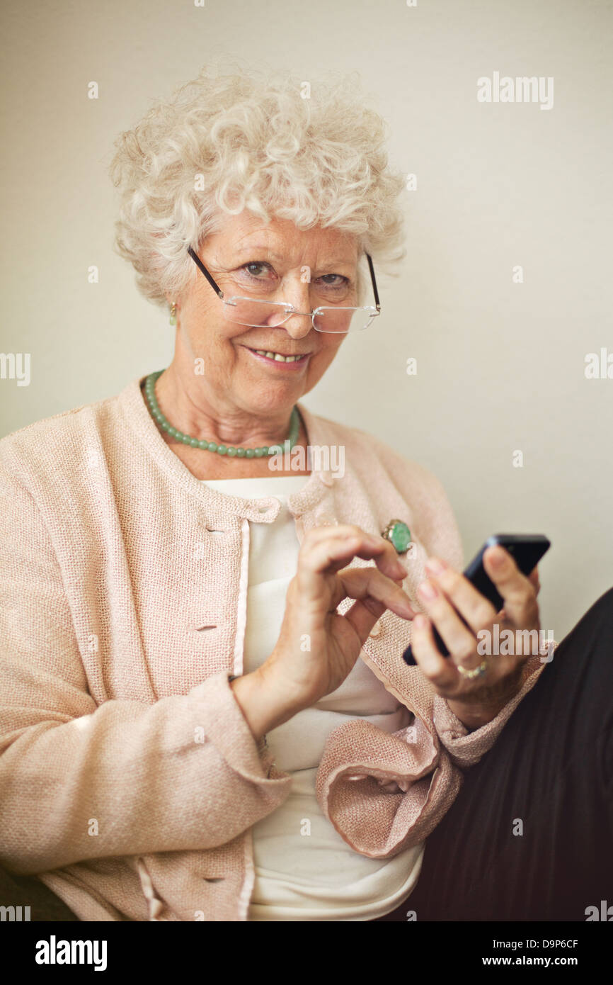Old lady texting someone using her cell phone - Stock Image