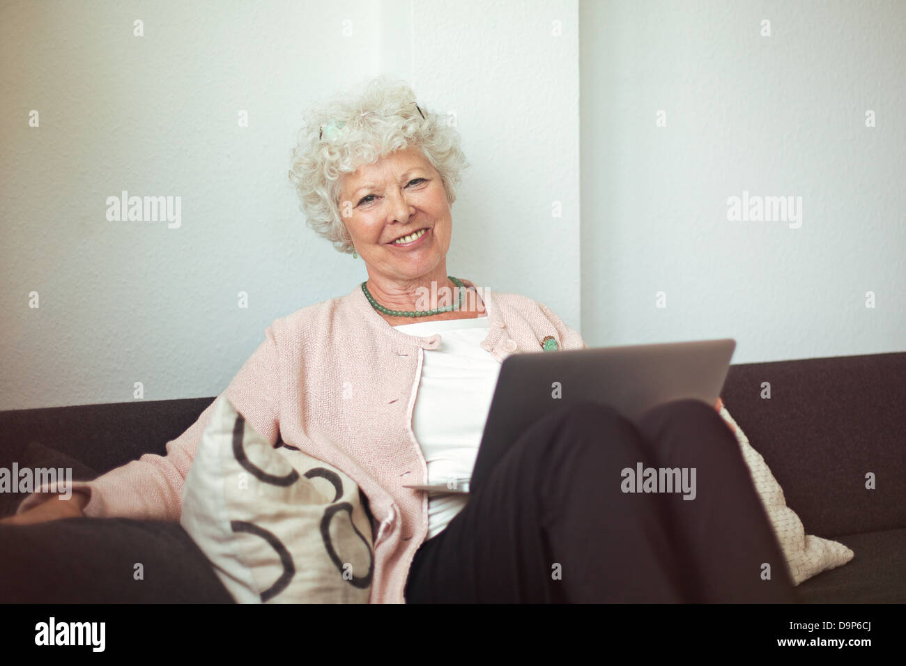 Happy senior woman sitting on the couch at home with laptop - Stock Image