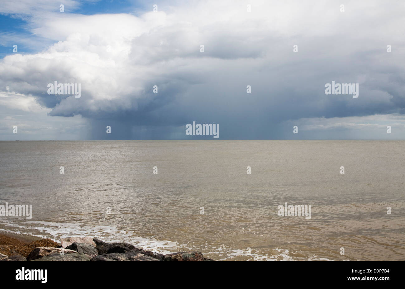 Heavy rain showers falling on sea from nimbocumulus cloud Orford Ness, North Sea, Suffolk coast, England - Stock Image