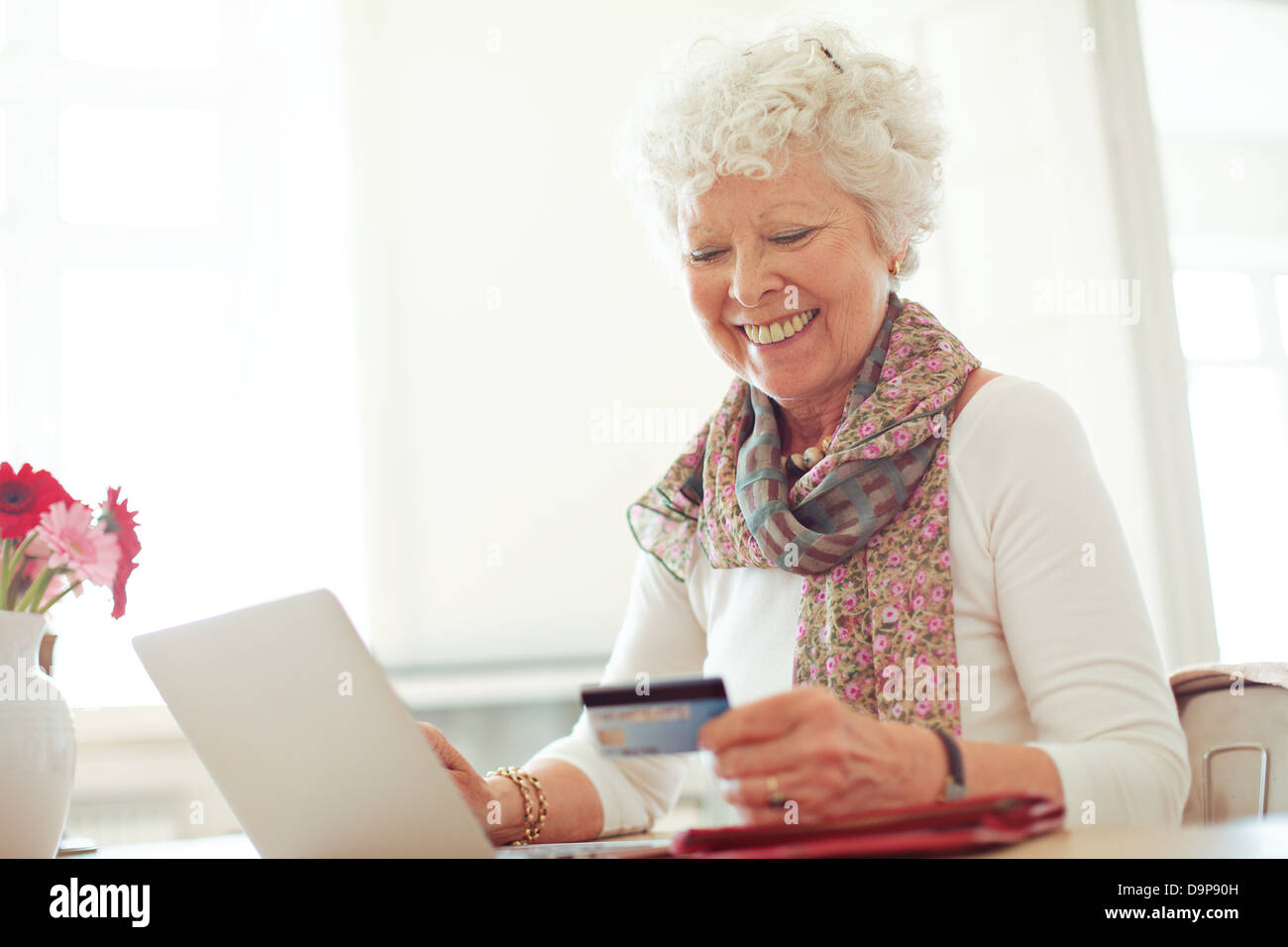 Old woman happy doing her shopping online using a credit card - Stock Image