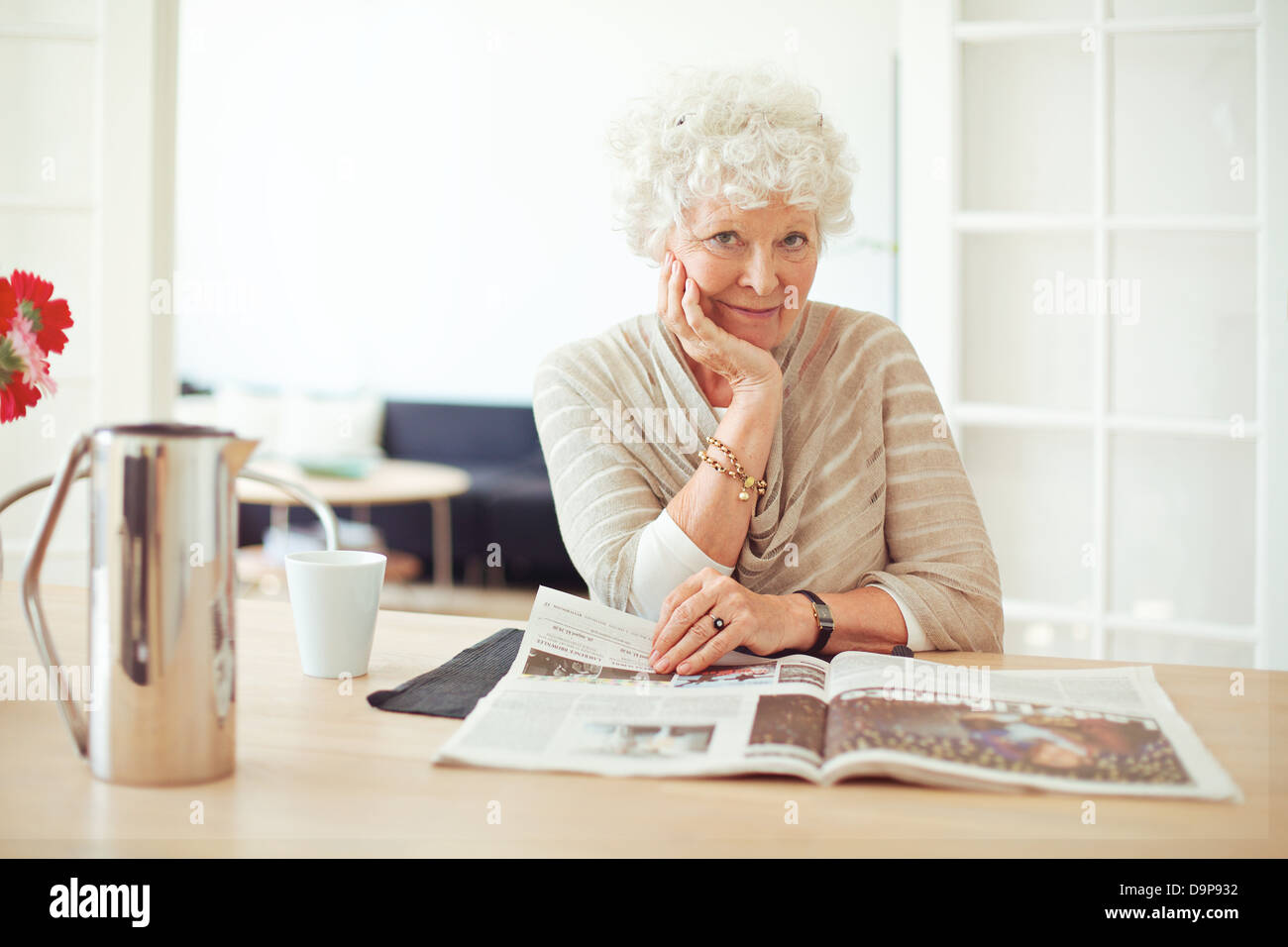 Portrait of a stylish old woman at home reading a magazine - Stock Image