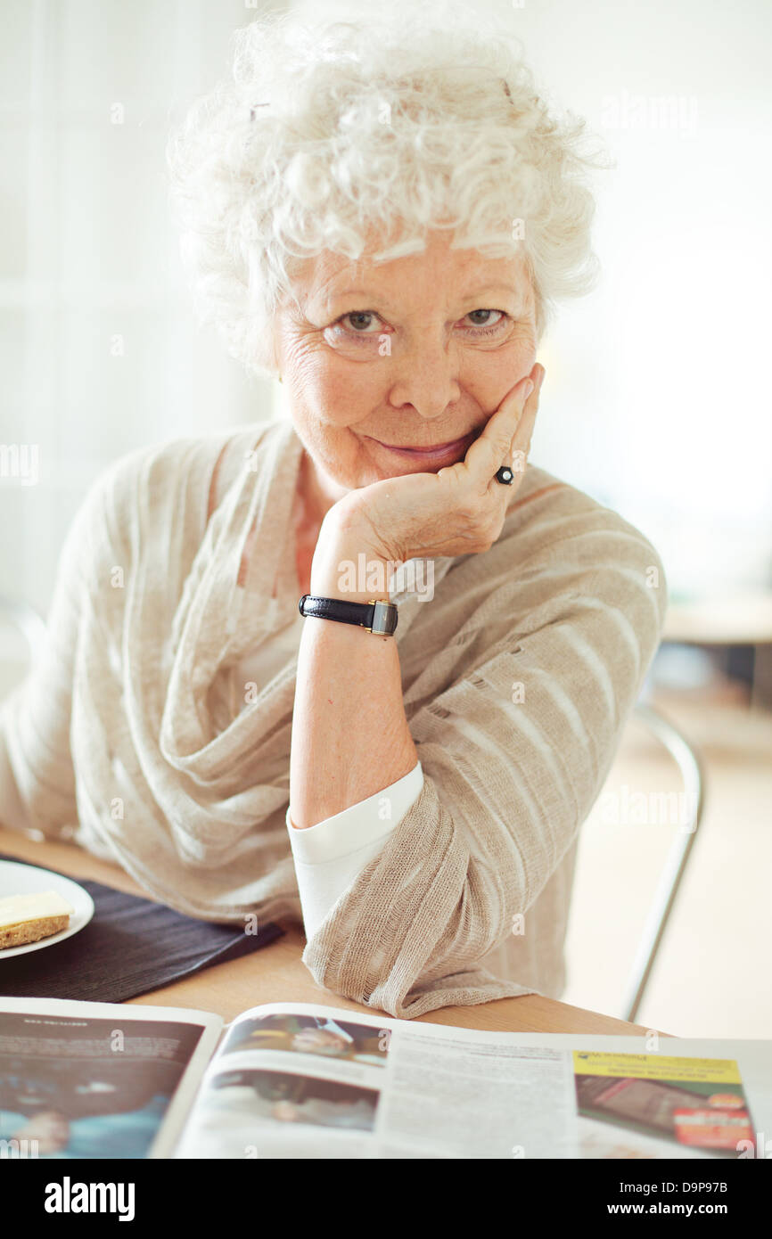 Portrait of a senior woman looking at you with hand on chin - Stock Image