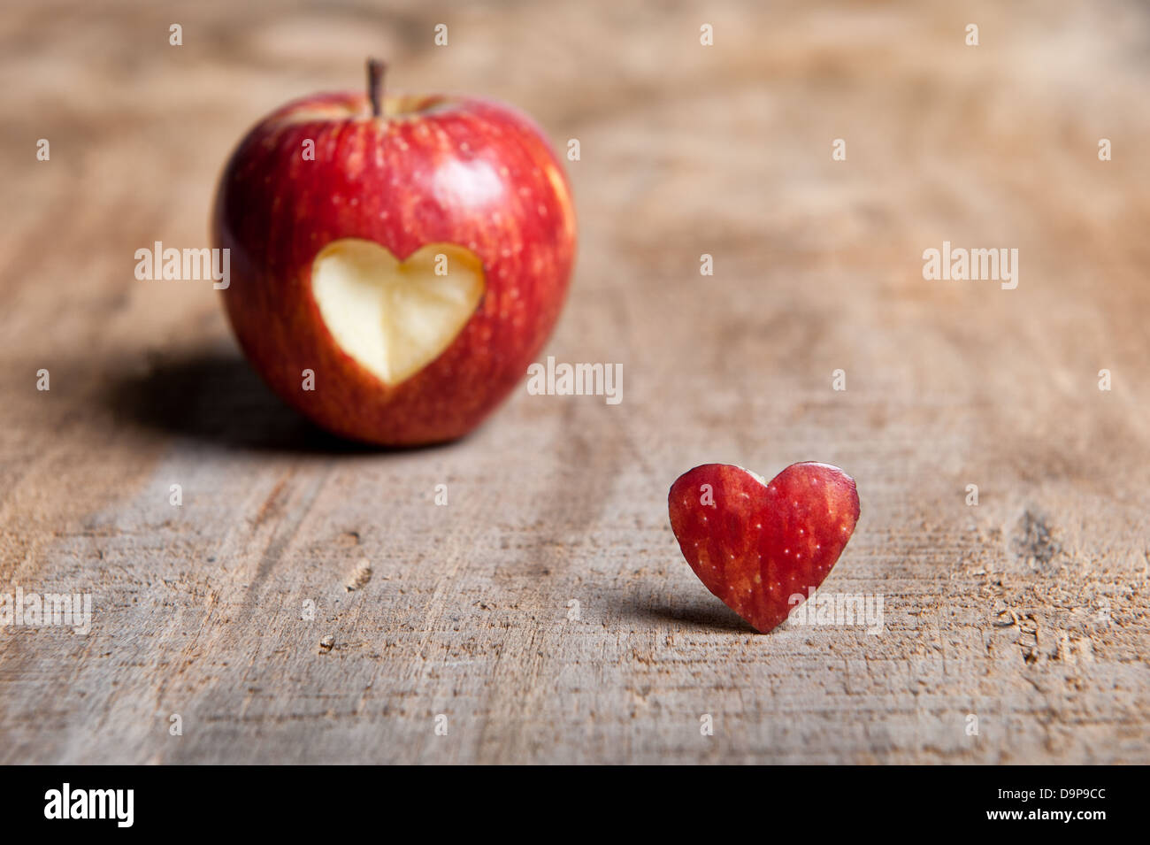 Red Apple With Heart Shape Cut Out The Is Placed In Front Next To On A Warm Toned Wooden Surface Love