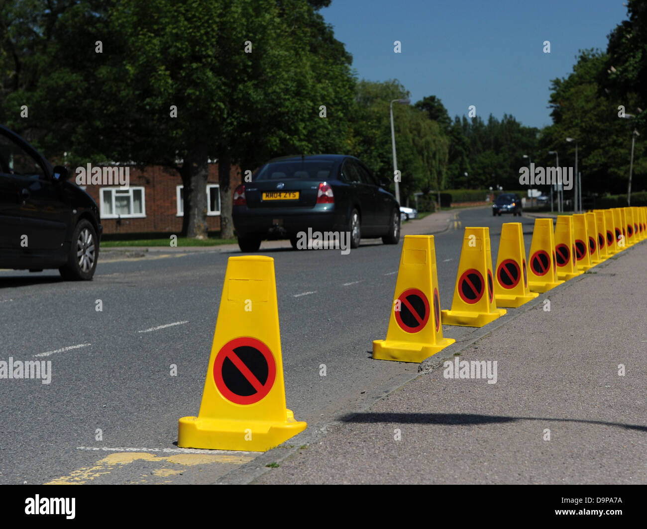 A line of no parking traffic cones on a main road. - Stock Image