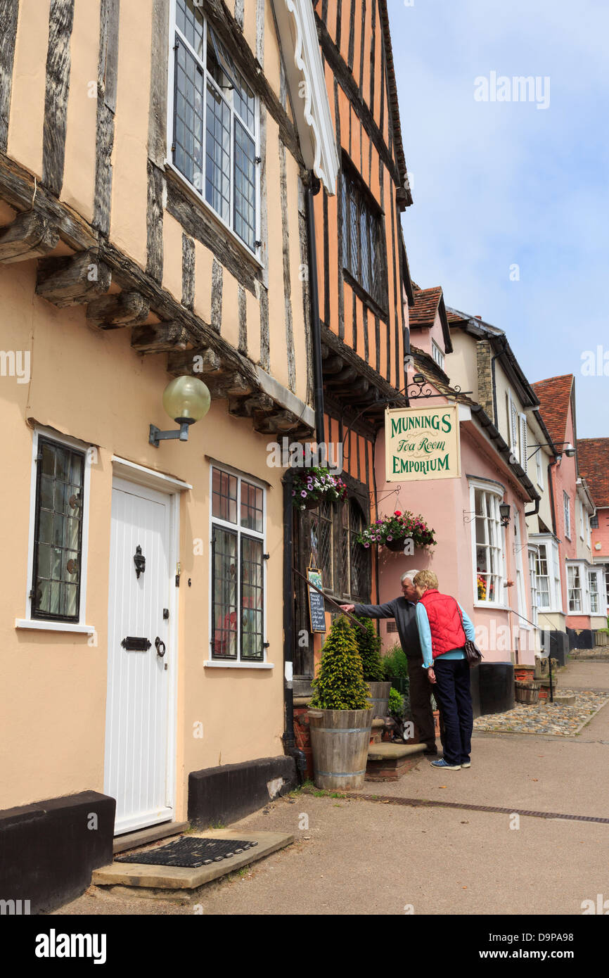 Two people studying the menu outside Munnings Tea Room Emporium in historic village centre. High Street Lavenham - Stock Image