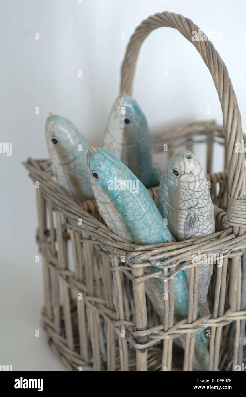 Fish figurines in wicker basket - Stock Image