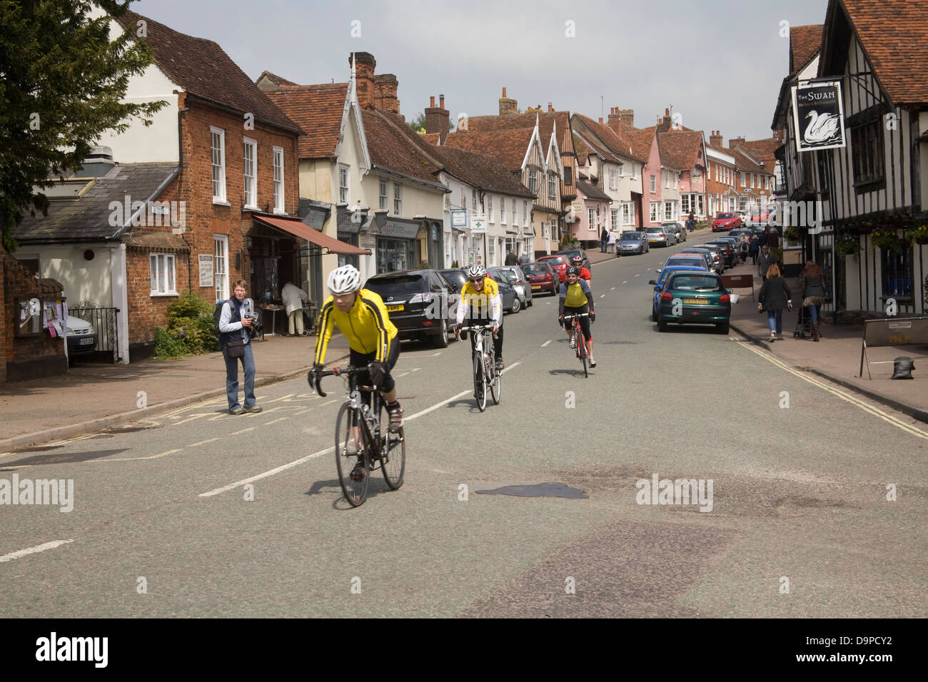 Lavenham Suffolk East Anglia England Group of cyclists cycling along High Street of medieval village - Stock Image