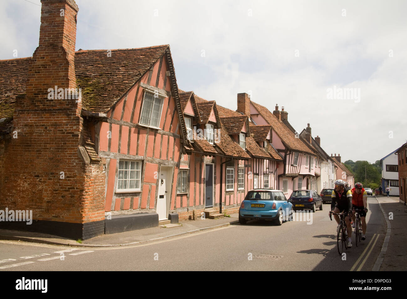 Lavenham Suffolk East Anglia England Two cyclists cycling past terrace of pastel coloured half timbered houses medieval - Stock Image