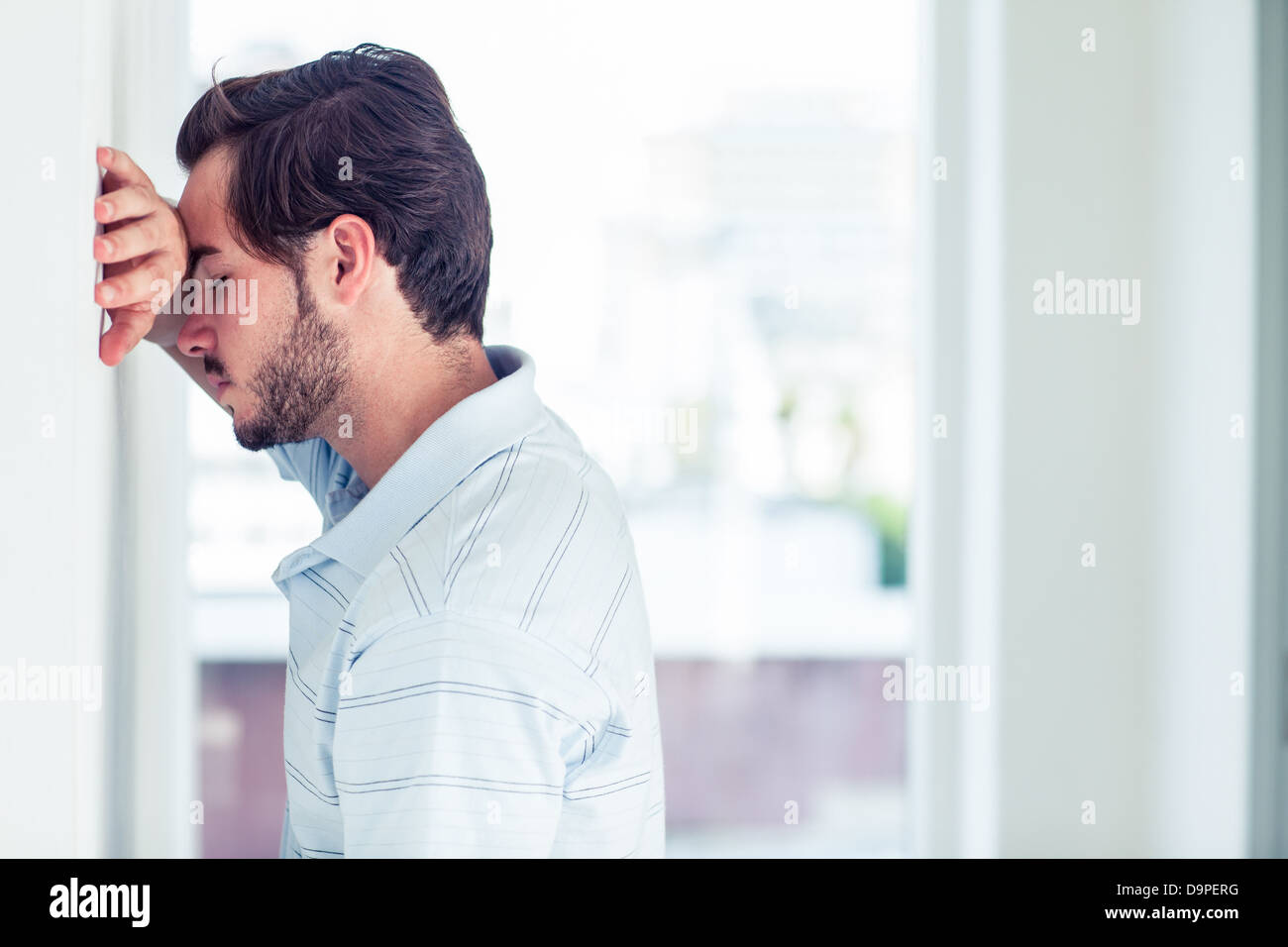 Stressful man leaning on the wall - Stock Image
