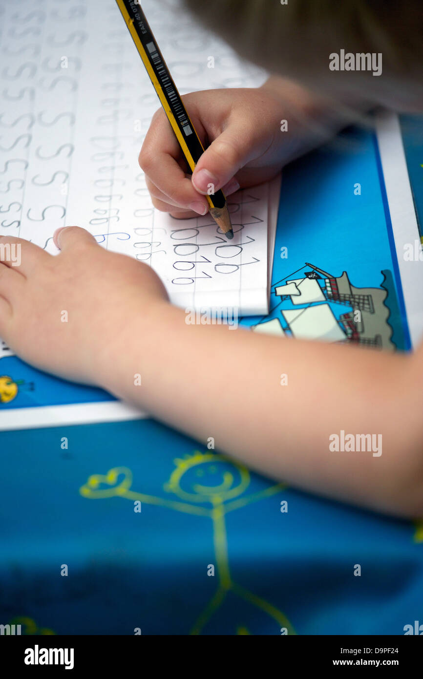Close up of a UK primary school child doing handwriting practice. - Stock Image