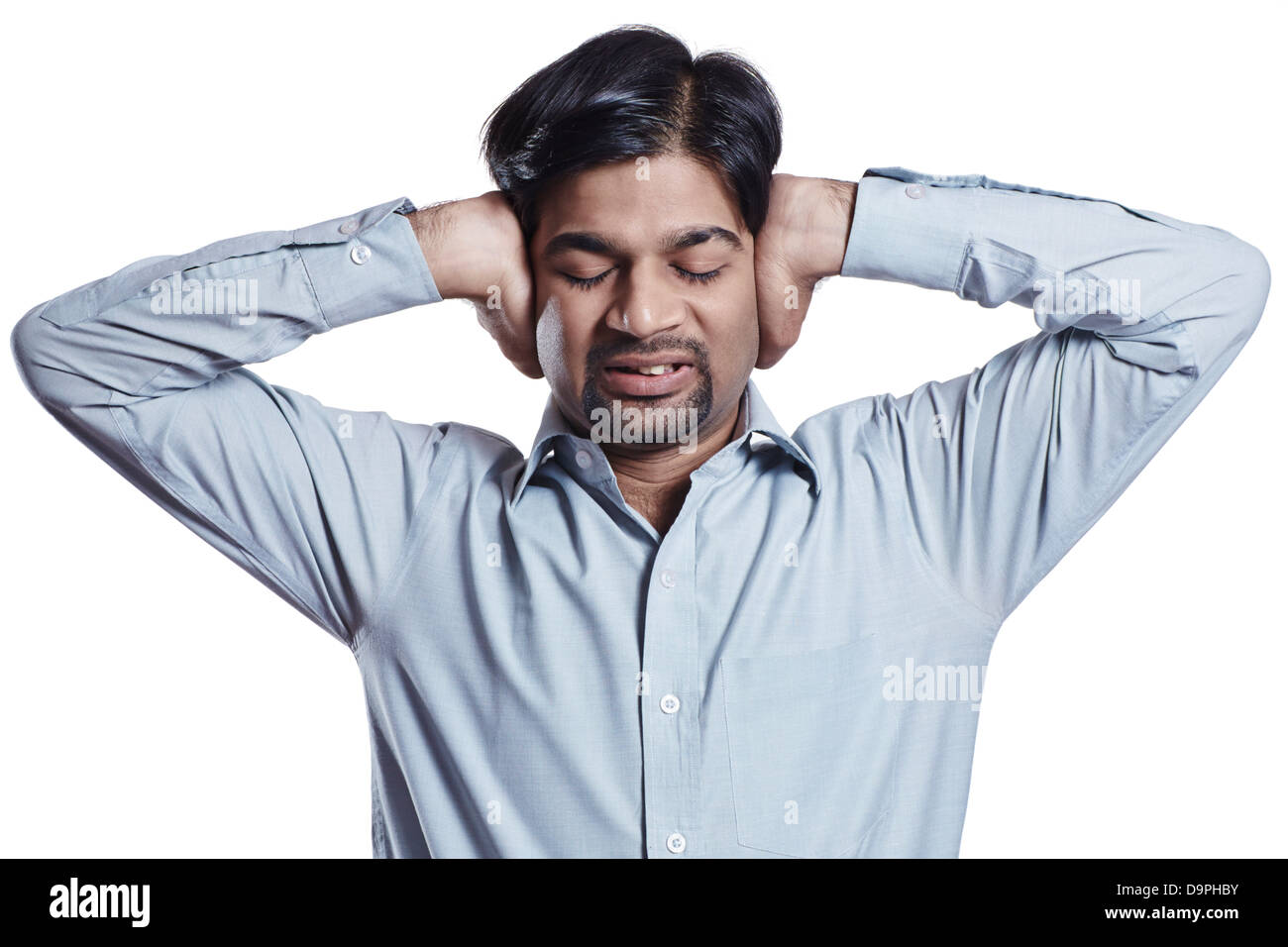 Businessman with hands covering ears - Stock Image