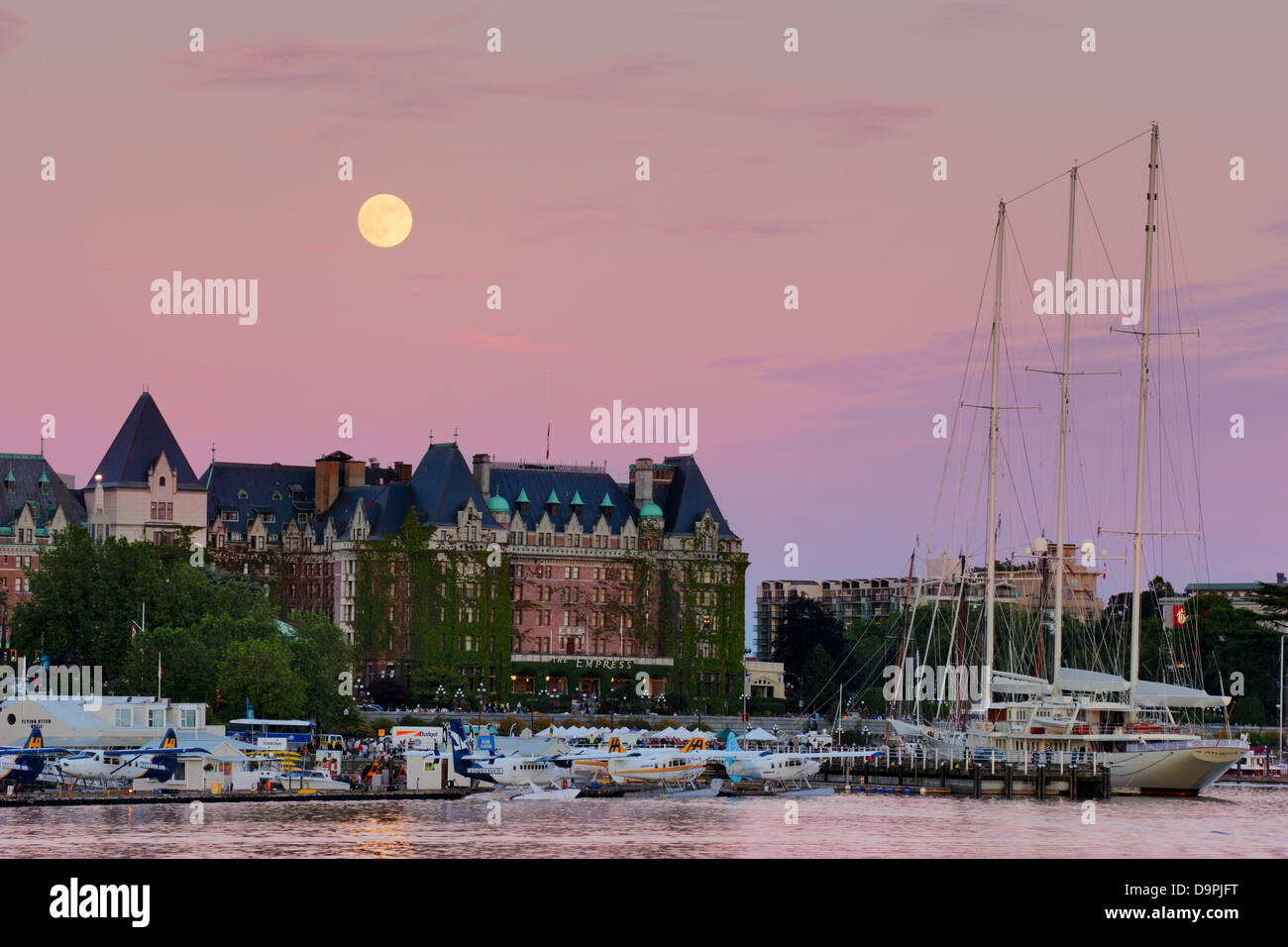 Full moon rising behind Empress hotel and luxury yacht Athena  at dusk-Victoria, British Columbia, Canada. - Stock Image