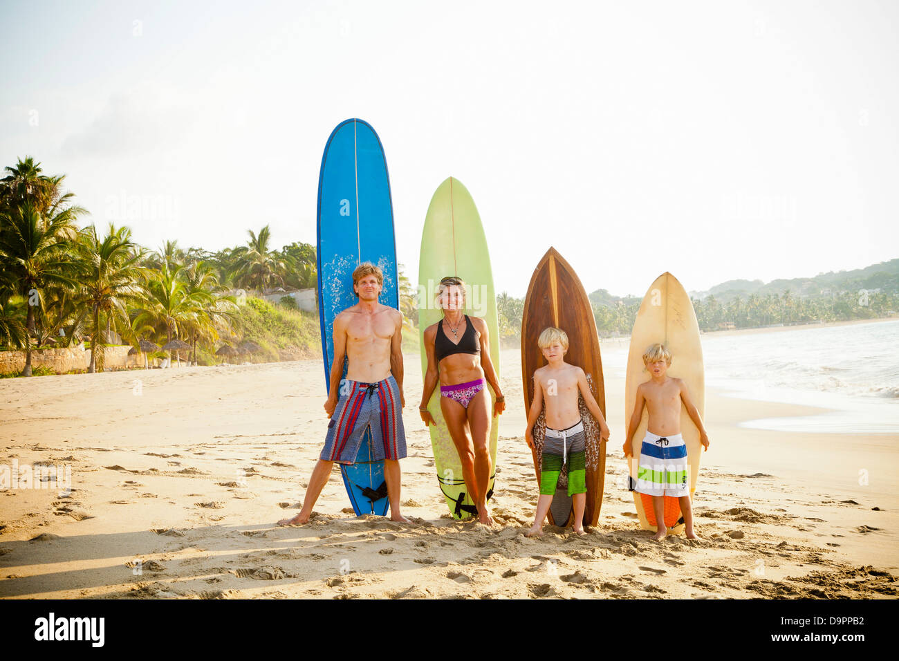 Family standing on beach with surfboards Stock Photo
