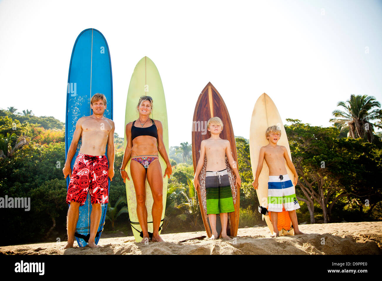 Family of four standing in front of surfboards Stock Photo