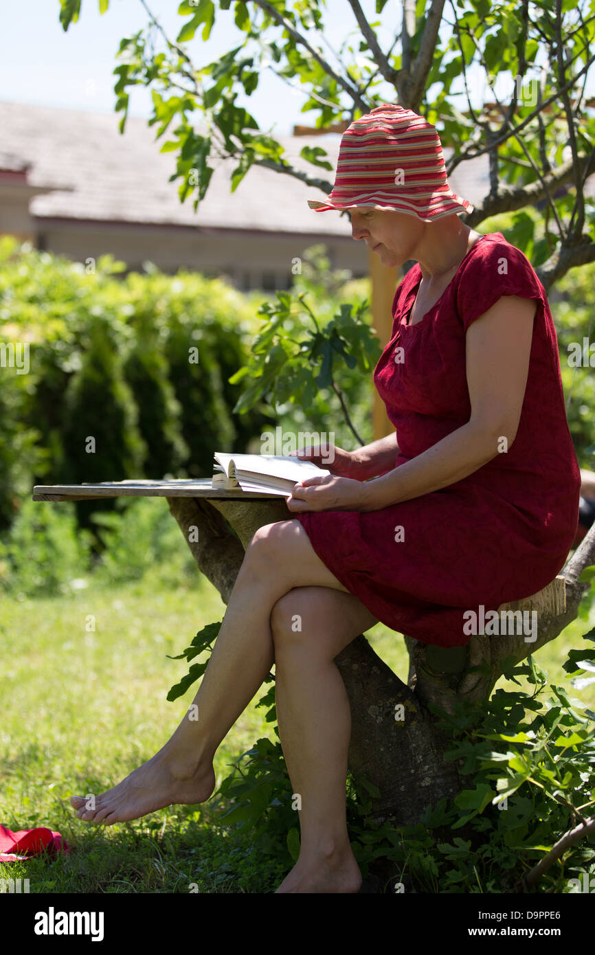 Calm modern senior woman reading book in her garden. - Stock Image
