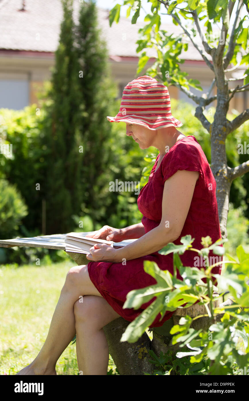 Serene modern aged woman reading book in her garden. - Stock Image